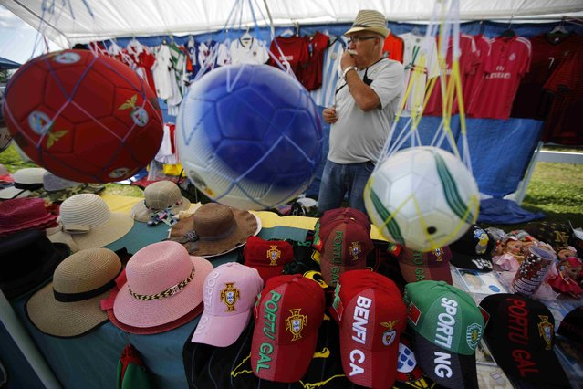 """Anton Parreira awaits customers to his booth displaying Portuguese soccer balls and clothing during the intermission at an Azorean """"tourada a corda"""" (bullfight by rope) in Brampton, Ontario August 15, 2015. (Photo by Chris Helgren/Reuters)"""