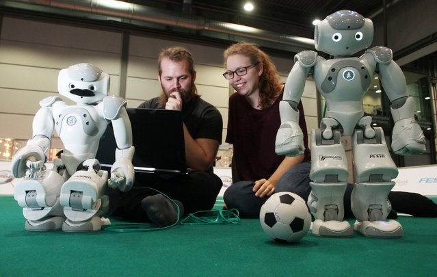 Jonathan Brast and Sina Ditzel work with a laptop on the functions of a robot that can play soccer in a hall on the fairgrounds in Leipzig, Germany, June 29, 2016. (Photo by Sebastian Willnow/EPA)