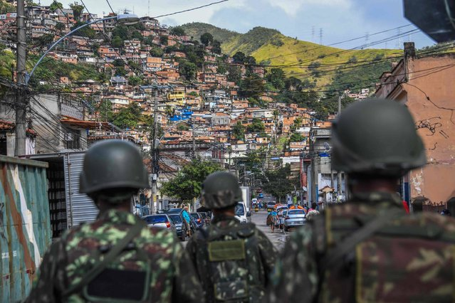 Soldiers take part in a crackdown on crime gangs, at the Lins de Vasconcelos slum complex in Rio de Janeiro, Brazil, on August 5, 2017. Thousands of Brazilian army troops raided Rio de Janeiro slums leaving parts of the city looking like a war zone. Their main goal was to stop gangs behind a surge in brazen robberies of commercial trucks, with arrest warrants issued for 40 people. However, the unusually aggressive pre-dawn operation also follows wider concerns that nearly bankrupt post-Olympic Rio is spinning out of control. (Photo by Apu Gomes/AFP Photo)