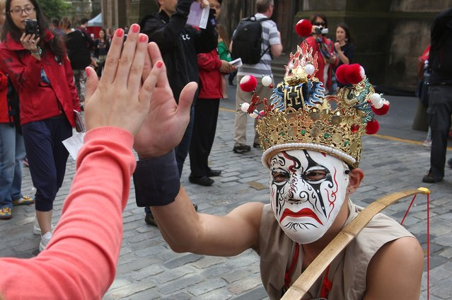 A jester gives a creepy high five to a member of the crowd on the Royal Mile. (Photo by David Cheskin/PA Wire)
