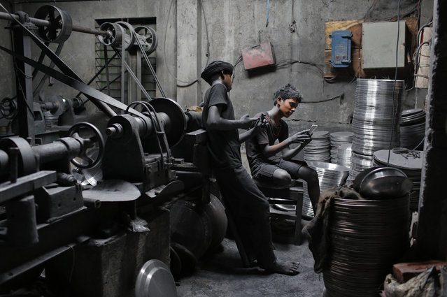 In this Sunday, June 12, 2016, photo, boys Imran, 11, left, and Nizam, 11, look at a mobile phone, as they take a break during their work at a factory that makes metal utensils in Dhaka, Bangladesh. (Photo by A.M. Ahad/AP Photo)