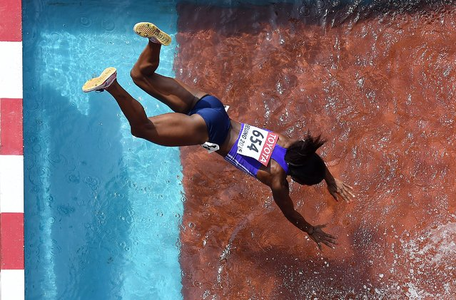 """Panama's Rolanda Bell falls into the water jump during the heats of the women's 3,000 metres steeplechase athletics event at the 2015 IAAF World Championships at the """"Bird's Nest"""" National Stadium in Beijing on August 24, 2015. (Photo by Antonin Thuillier/AFP Photo)"""