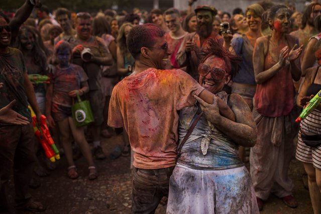 Revelers dance after throwing  coloured powders on each other during a Monsoon Holi Festival in Madrid, Spain, Saturday, August 9, 2014. The festival is based on the Hindu spring festival Holi, also known as the festival of colours where participants colour each other with dry powder and coloured water. (Photo by Andres Kudacki/AP Photo)