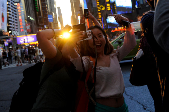 """People take a selfie as the sun sets over Manhattan aligned exactly with the streets in a phenomenon known as """"Manhattanhenge"""", in New York City, U.S., July 11, 2016. (Photo by Mark Kauzlarich/Reuters)"""