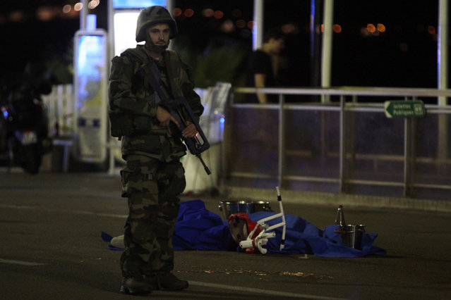 A soldier stands next to a dead body covered with a blue sheet on the Promenade des Anglais seafront in the French Riviera town of Nice on July 15, 2016, after a van drove into a crowd watching a fireworks display. At least 75 people were killed when a truck drove into a crowd watching a fireworks display in the French resort of Nice, a lawmaker said on July 15. (Photo by Valery Hache/AFP Photo)