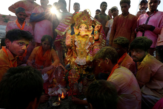 Devotees offer prayers at an idol of the Hindu god Ganesh, the deity of prosperity, before its immersion into the Yamuna river on the last day of the Ganesh Chaturthi festival in Delhi, India September 5, 2017. (Photo by Cathal McNaughton/Reuters)