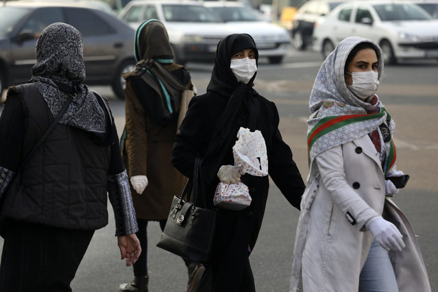 """Pedestrians wearing face masks cross a square in western Tehran, Iran, Saturday, February 29, 2020. Iran is preparing for the possibility of """"tens of thousands"""" of people getting tested for the new coronavirus as the number of confirmed cases spiked again Saturday, Health Ministry spokesman Kianoush Jahanpour said, underscoring the fear both at home and abroad over the outbreak in the Islamic Republic. (Photo by Vahid Salemi/AP Photo)"""