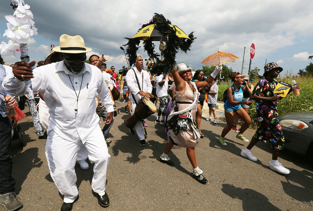 People march through the Lower Ninth Ward during a second line parade on the 10th anniversary of Hurricane Katrina on August 29, 2015 in New Orleans, Louisiana. (Photo by Mario Tama/Getty Images)