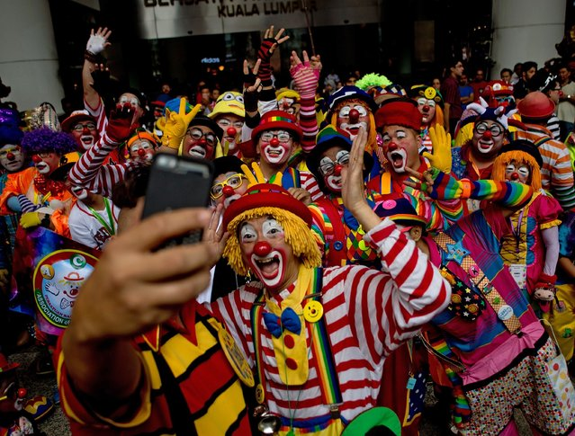 Clowns pose for a selfie after a parade during the Clown Festival in Kuala Lumpur on August 17, 2014.  Around 80 clowns from all over Malaysia took part in the event organised by the Association of Clowns Malaysia to provide a platform for clown education, acquiring new skills and offering members support. (Photo by Manan Vatsyayana/AFP Photo)