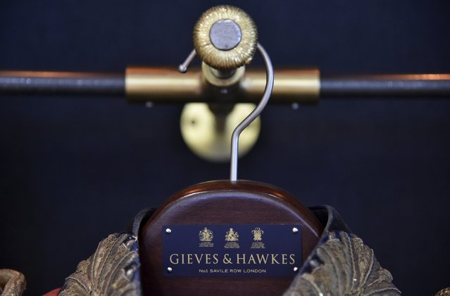 A clothes hanger with the royal warrant insignia is seen at the Gieves and Hawkes headquarters  in central London, Britain, August 19, 2015. Gieves and Hawkes has contracts with British military forces and has a royal warrant to supply military uniforms and livery for Queen Elizabeth. (Photo by Toby Melville/Reuters)