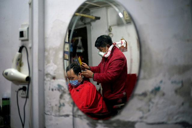 Yang Guangyu, 54, a local barber working in his shop at a blocked residential area, wears his handmade mask assembled from a water bottle, mask and a plastic pipe, as he works after the lockdown was lifted in Wuhan, capital of Hubei province and China's epicentre of the novel coronavirus disease (COVID-19) outbreak on April 11, 2020. (Photo by Aly Song/Reuters)