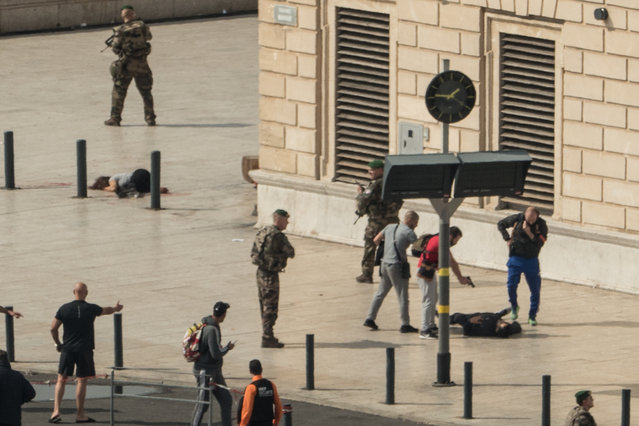 French police point a gun at a man on the ground (C) as a stabbed woman lies (L) while soldiers secure the area following an attack on October 1, 2017 at the Saint-Charles main train station in the French Mediterranean city of Marseille. A suspected Islamist knifeman killed two women at the main train station in Marseille on October 1 before being shot dead by soldiers on patrol, local officials and police said. (Photo by Paul-Louis Leger/AFP Photo)