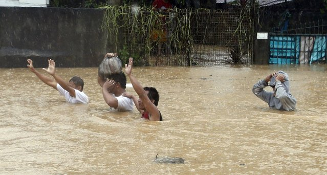 Flood victims wave to a rescue boat as they wade chest deep, through a flooded road in Marikina, metro Manila, September 19, 2014. (Photo by Erik De Castro/Reuters)