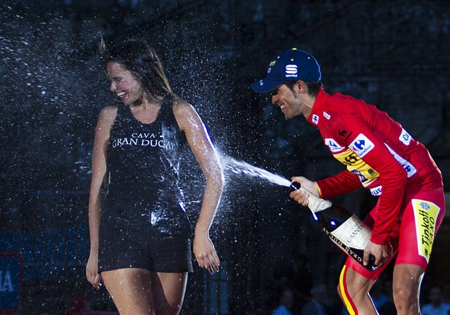 """Tinkoff's Spanish cyclist Alberto Contador sprays cava on a hostess as he celebrates on the podium after winning the 69th edition of """"La Vuelta"""" Tour of Spain in Santiago de Compostela on September 14, 2014. (Photo by Jaime Reina/AFP Photo)"""