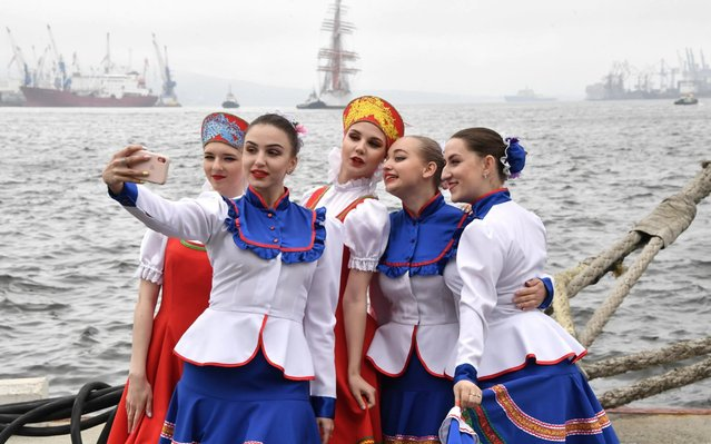 Young women in Cossack costume pose for a photograph in the port of Vladivostok, Russia on June 3, 2020 during a ceremony marking the arrival of the tallship Pallada from a round-the-world voyage. At the end of 2019, three ships of Rosrybolovstvo – the Pallada, the Kruzenshtern, and the Sedov – started a round-the-world voyage to mark the 200th anniversary of the discovery of Antarctica by Bellingshausen and Lazarev, and the 75th anniversary of Soviet victory in the 1941-45 Great Patriotic War. The Pallada and the Sedov arrived in Vladivostok on 3 June 2020. (Photo by Yuri Smityuk/TASS)