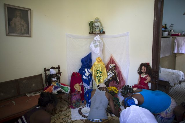 Followers of the Afro-Cuban religion Santeria pray for the spirits in front of an altar and an image of Jesus Christ before a ceremony in a house known as Cabildo, or religious house by Santeria tradition, in downtown Havana, August 7, 2015. (Photo by Alexandre Meneghini/Reuters)
