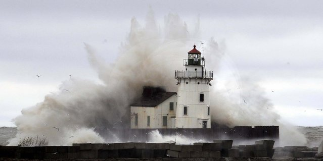 Waves pound a lighthouse on the shores of Lake Erie near Cleveland as high winds spinning off the edge of superstorm Sandy took a vicious swipe at northeast Ohio early Tuesday. (Photo by Tony Dejak/Associated Press)