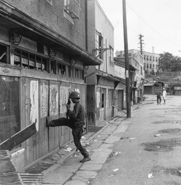 A South Korean soldier kicks his way into a building in Inchon, in his search for Communists who have gone into hiding since the American invasion of the Korean port, October 1950. (Photo by Bert Hardy/Picture Post/Getty Images)