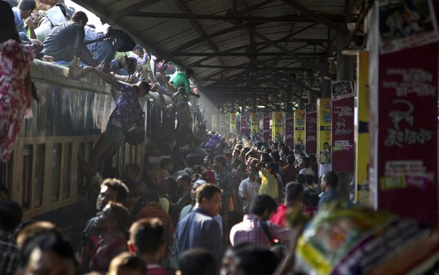 Bangladeshi Muslims try to climb on to the roof of an overcrowded train as they head to their homes ahead of Eid al-Adha in Dhaka, Bangladesh, Friday, October 3, 2014. Muslims around the world are preparing to celebrate Eid al-Adha, a three-day holiday that starts Saturday, commemorating the willingness of the prophet Ibrahim or Abraham as he is known in the Bible to sacrifice his son in accordance with God's will, though in the end God provides him a sheep to sacrifice instead. (Photo by A. M. Ahad/AP Photo)