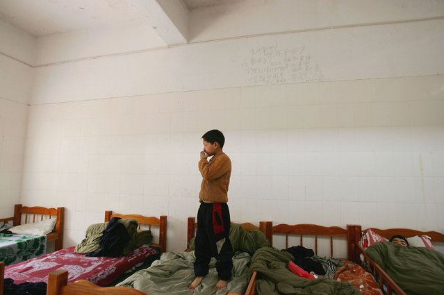 A kid stands on his bed at an assistance center February 23, 2005 in Shenzhen, Guangdong Province, China. (Photo by Cancan Chu/Getty Images)