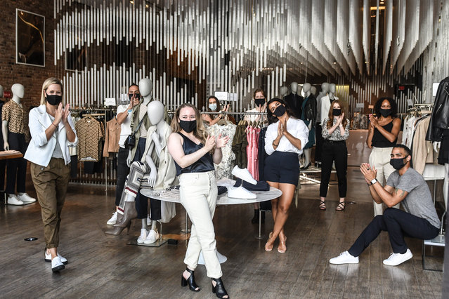 Workers inside of a Reiss store clap as they are back at work on June 22, 2020 in the SoHo neighborhood in New York City. New York City enters phase 2 reopening with the reopening of retails stores, outdoor dining and barbershops. The city estimates as many as 400,000 people will return to work next month as coronavirus restrictions are lifted. (Photo by Stephanie Keith/Getty Images)