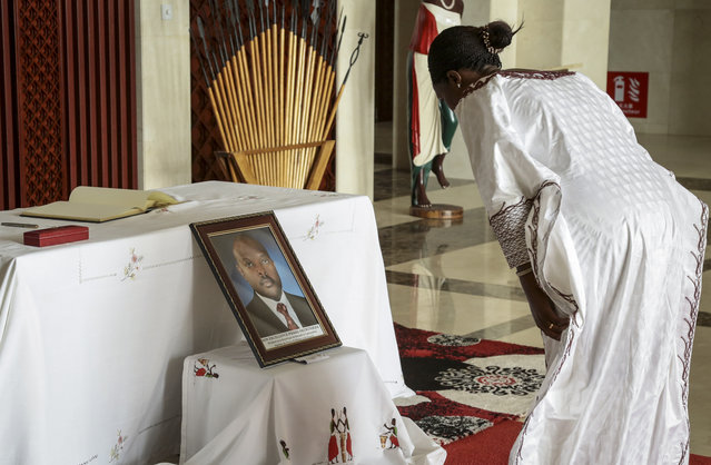 An unidentified dignitary pays her respects after signing the book of condolences in front of a photograph of the late President Pierre Nkurunziza, at the presidential palace in Bujumbura, Burundi Wednesday, June 10, 2020. Burundi's government said Tuesday, June 9, 2020 that President Pierre Nkurunziza had died of a heart attack. (Photo by Berthier Mugiraneza/AP Photo)