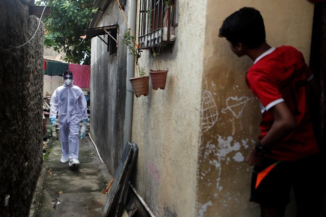 A healthcare worker wearing personal protective equipment (PPE) walks in an alley of a slum area during a check-up camp for the coronavirus disease (COVID-19) in Mumbai, India June 27, 2020. (Photo by Francis Mascarenhas/Reuters)