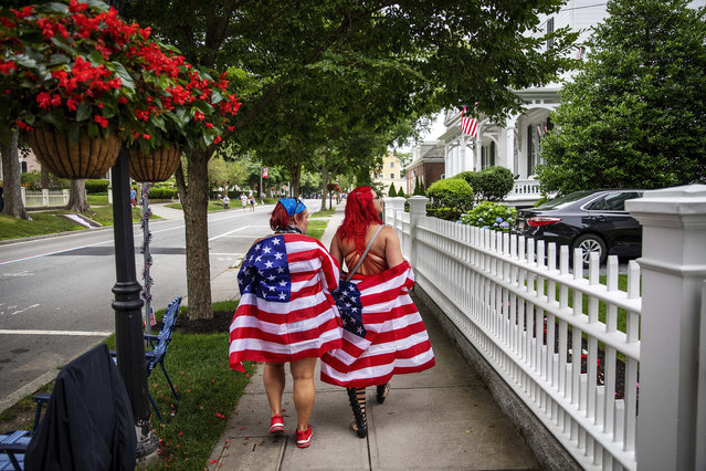 Parade goers draped in American flags walk down the street before a Fourth of July parade begins Saturday, July 4, 2020, in Bristol, R.I. The town, which lays claim to the nation's oldest Independence Day celebration in the country, held a vehicle-only scaled down version of its annual parade Saturday due to the coronavirus pandemic. (Photo by David Goldman/AP Photo)
