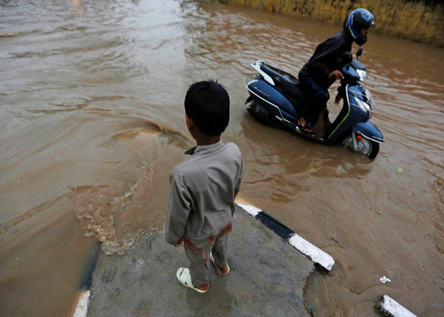 A boy stands on a divider as a man pushes his scooter through a flooded street during heavy rains in New Delhi, India, August 29, 2016. (Photo by Adnan Abidi/Reuters)