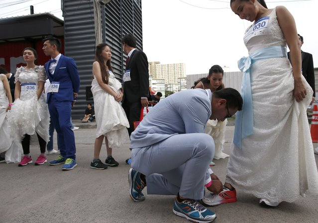 """A Thai groom-to-be does up his bride-to-be shoelaces before competing in the """"Running of the Brides"""" event in Bangkok, Thailand, 02 December 2017. (Photo by Rungroj Yongrit/EPA/EFE/Rex Features/Shutterstock)"""