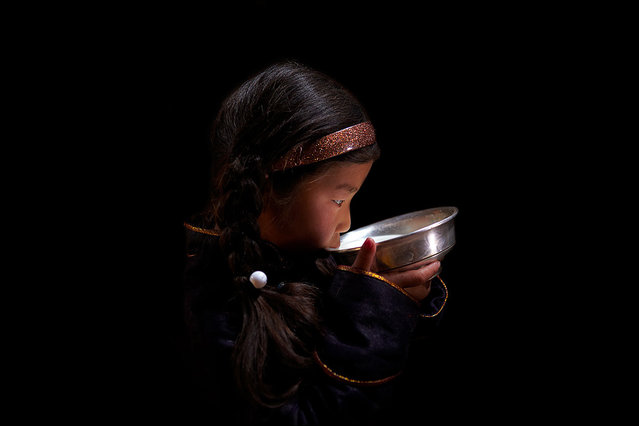 """Young Girl Drinking Mares Milk: Fermented mares milk (Airag) is the traditional national beverage of Mongolia. The amount of milk produced by one mare averages about two litres when milked six times per day, so in order to make enough Airag for the family and any visitors, it is necessary to have at least a dozen mares. To get good quality Airag, it is necessary to stir the milk mix no less than 1,000 times each day! Produced during the summer months in a specially made hide skin bag, fresh Airag is quite mild but if kept for long enough it turns sour and acidic which is how many Mongolian's prefer it"". (Photo and comment by Andrew Newey/National Geographic Photo Contest via The Atlantic)"