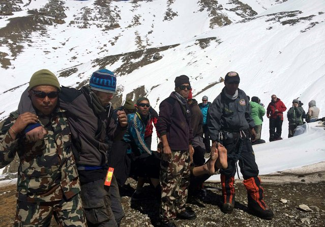 A handout picture made available by the Nepalese Army shows members of the army rescue unidentified trekkers from the Thorung La mountain pass on the Annapurna Circuit, near Muktinath, in Mustang district, Nepal, 17 October 2014. (Photo by EPA/Nepalese Army)