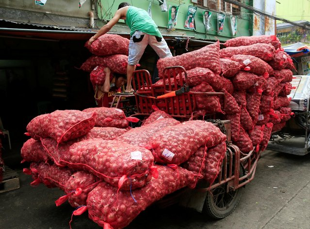 A worker helps his colleague carry sacks of red onions which they deliver to a warehouse in Metro Manila, Philippines July 4, 2016. (Photo by Romeo Ranoco/Reuters)