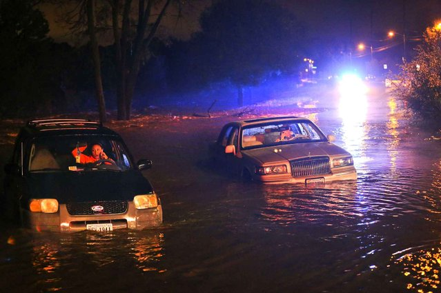 Ashley Hill, left, and John Joplin make calls from their car as they wait to be rescued Tuesday, September 29, 2015, in Roanoke, Va. Steady rains have forced the early closure of schools and flooded streets from Southside Virginia to the Shenandoah Valley and surrounding areas. (Photo by Heather Rousseau/The Roanoke Times via AP Photo)