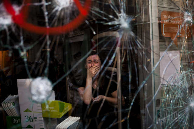 Mirian Burrueco, 30, reacts behind the broken glass of her shop stormed by demonstrators during clashes with the police at the general strike in Barcelona, Thursday, March 29, 2012. Spanish workers livid over labor reforms they see as flagrantly pro-business staged a nationwide strike Thursday and tried to bring the country to a halt by blocking traffic, closing factories and clashing with police in rowdy demonstrations. (Photo by Emilio Morenatti/AP Photo)