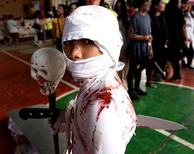 A boy wears a mummy costume during a Zombie Zumba Party in Mandaluyong City, the Philippines, October 26, 2014. Around 500 people in various halloween costumes participated in Zombie Zumba Party, which is one of the city's efforts to promote a healthy lifestyle as part of the Halloween celebration. (Photo by Rouelle Umali/Xinhua)