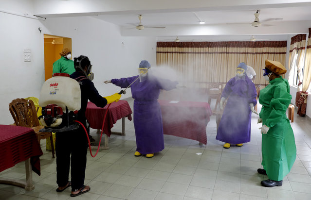 Sri Lankan municipal health workers are disinfected after a swab sample collecting session to test for COVID-19 in Colombo, Sri Lanka, Tuesday, July 14, 2020. (Photo by Eranga Jayawardena/AP Photo)
