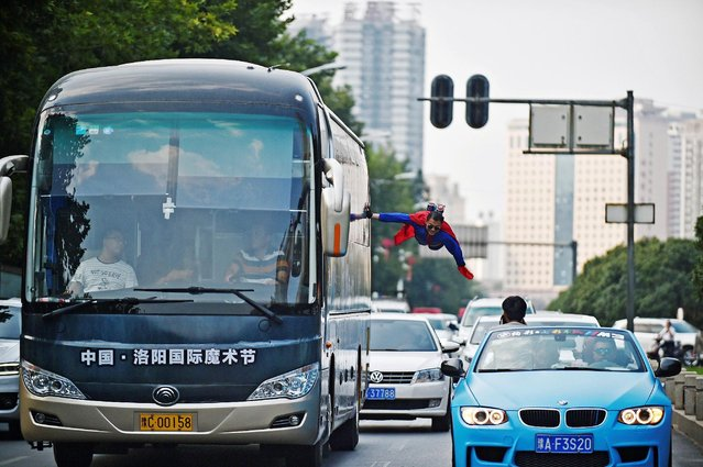 A performer is seen floating in mid-air as he holds onto a moving bus during an International Magic Festival in Luoyang, Henan province, China September 11, 2016. (Photo by Reuters/China Daily)