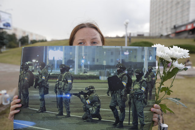 A woman holds a picture of Belarusian police as people stand near the place where Alexander Taraikovsky died amid the clashes protesting the election results, in Minsk, Belarus, Monday, August 24, 2020. Belarusian authorities on Monday detained two leading opposition activists who have helped spearhead a wave of protests demanding the resignation of the country's authoritarian ruler of 26 years. (Photo by Dmitri Lovetsky/AP Photo)