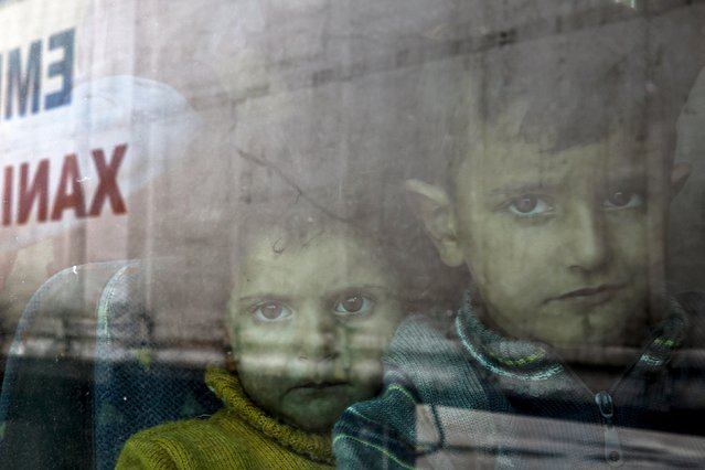Syrian children are seen inside a bus following their arrival by the Eleftherios Venizelos passenger ferry with over 2,500 migrants and refugees from the island of Lesbos at the port of Piraeus, near Athens, Greece, October 8, 2015. Refugee and migrant arrivals to Greece this year will soon reach 400,000, according to the UN Refugee Agency (UNHCR). (Photo by Yannis Behrakis/Reuters)