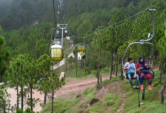 Tourists sit on chairlifts at the Patriata Resort near Murree, some 65 km form Islamabad on August 16, 2020, after the government announced most of the country's remaining restrictions would be lifted following the drop in COVID-19 coronavirus new cases for several weeks. (Photo by Aamir Qureshi/AFP Photo)