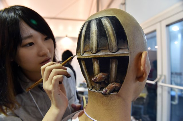 "This picture taken on November 1, 2014 shows Japanese body-painting artist Hikaru Cho (L) adding the finishing touches to a body painting of fingers sticking out from prison cell bars on the head of Ryonosuke Tanaka during ""Tokyo Designers Week"" in Tokyo. Cho, 21, was born to Chinese parents in Japan and burst onto Tokyo's art scene when she entered the city's Musashino Art University in 2012. (Photo by Yoshikazu Tsuno/AFP Photo)"