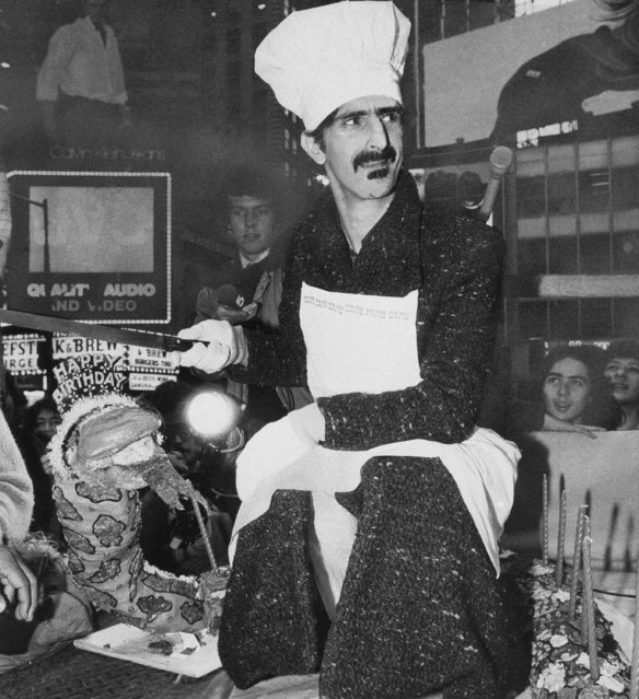 """Rock star Frank Zappa, wearing a chef's cap, cuts a 20-foot-long cake shaped like a snake, outside a Times Square movie house where his film """"Baby Snakes"""" was premiering, December 21, 1979 in New York City. The cake, served to passers by from a flatbed truck, was to mark Zappa's 39th birthday. (Photo by Carlos Rene Perez/AP Photo)"""