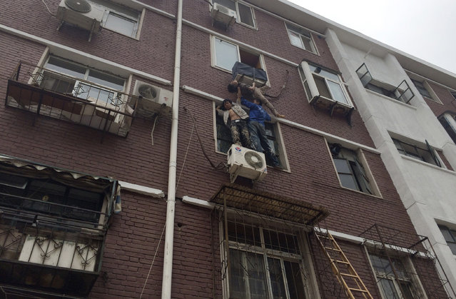 Liu Xinjun (L) and Jia Xiaoyu (R) hold a woman who fell out a window at her home in Tianjin, China, June 17, 2014. Liu and Jia held up an elderly who fell out her window and was stuck on a rack of an air-conditioner for five minutes, as another man Yang Ming held on to the woman with a rope from inside the room while waiting for firefighters to rescue. (Photo by Reuters/China Daily)