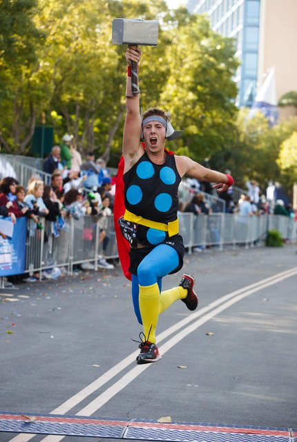 Jacob Boyer lifts his Thor hammer while leaping across the finish line during the Avengers Super Heroes Half Marathon in and around the Disney Parks in Anaheim, California November 16, 2014. (Photo by Eugene Garcia/Reuters)