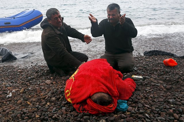 The body of a 65-year old Iraqi refugee woman is covered with a towel as her husband (R) and a relative mourn, following their arrival on the Greek island of Lesbos in a dinghy, after crossing a part of the Aegean Sea from the Turkish coast, October 16, 2015. According to the relatives, the woman drowned while the members of the family were forced violently by smugglers to leave the Turkish coasts in a dinghy that filled immediately with sea water. (Photo by Giorgos Moutafis/Reuters)