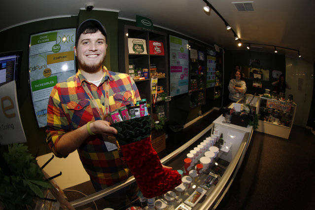 In this photograph taken on Thursday, November 20, 2014, bud tender Maxwell Bradford shows off holiday stocking filled with more than $500 of marijuana and accessories for sale for the holiday season in a recreational marijuana shop in northwest Denver. Colorado's nascent marijuana industry is employing techniques created by traditional retailers to entice cannabis users to spend their holiday money at the dispensaries. (Photo by David Zalubowski/AP Photo)