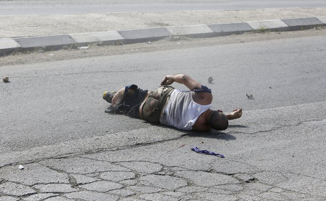An Israeli motorist is seen on the ground after he was struck by a Palestinian vehicle in the West Bank city of Hebron October 20, 2015. A Palestinian vehicle ran over and killed an Israeli motorist whom a Reuters photographer said was using a club to hit Palestinian protesters and cars on a roadside in the Israeli-occupied West Bank.(Photo by Mussa Qawasma/Reuters)