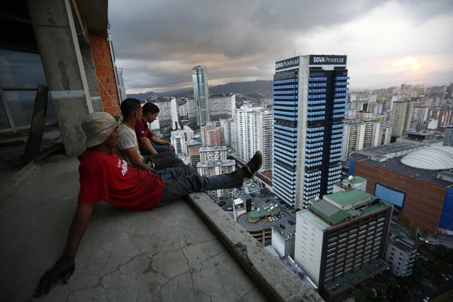 """Men rest after salvaging metal on the 30th floor of the """"Tower of David"""" skyscraper in Caracas in this February 3, 2014 file photo. The building was intended to be a shining new financial center but was abandoned around 1994 after the death of its developer and the collapse of the financial sector. Squatters invaded the huge concrete skeleton in 2007 and now about 3,000 people call the tower their home. The first time I tried to get access to the tower wasn't really a success. (Photo and caption by Jorge Silva/Reuters)"""