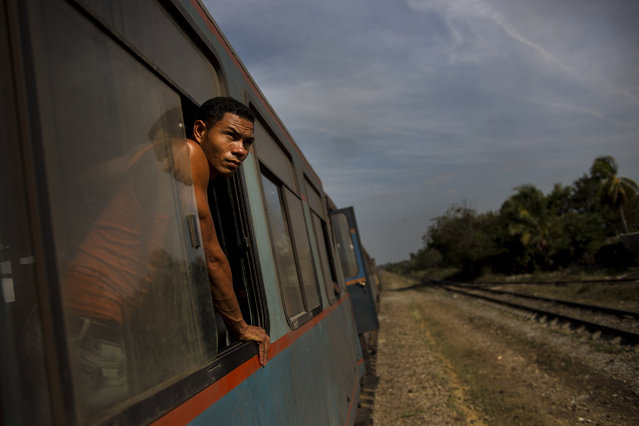 In this March 23, 2015 photo, a train passenger looks out at the countryside between Ciego de Avila and Santa Clara, Cuba. While the island is slowly modernizing its rail system, it remains the slowest way to get around already slow-moving Cuba. (Photo by Ramon Espinosa/AP Photo)